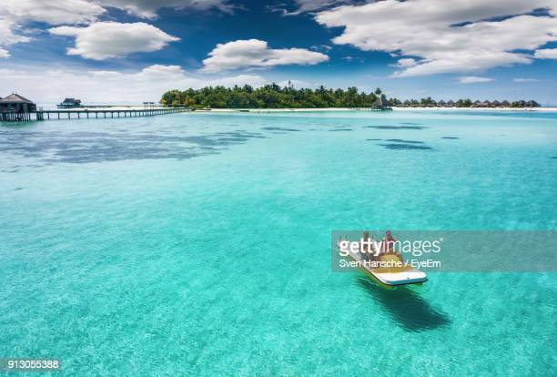 couple pedaling boat on sea against sky - pedal boat stock pictures, royalty-free photos & images