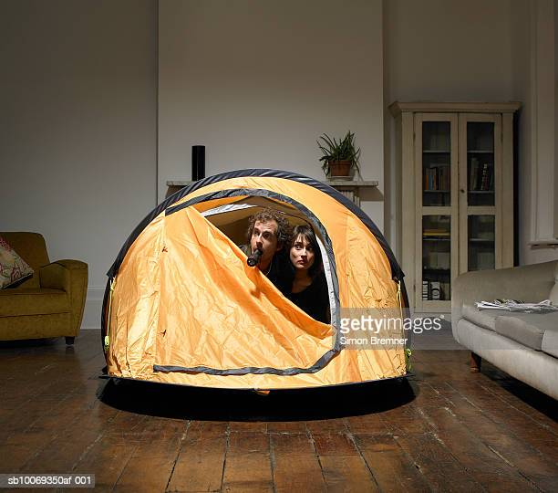 Couple peering from tent in living room