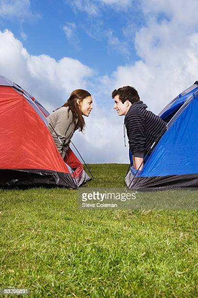 Couple peering out of adjacent tents