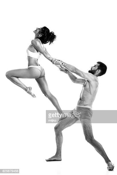 Couple performing acro-yoga exercise in studio