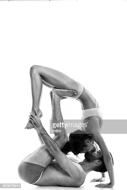 Couple performing acro-yoga exercise in studio