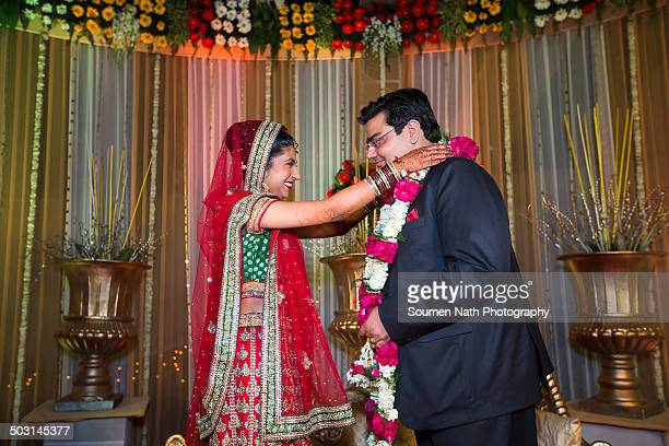 couple performing jaimala during their wedding. - ceremony stock pictures, royalty-free photos & images