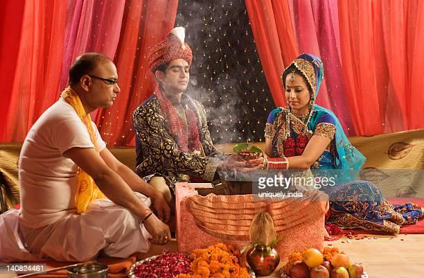 Couple performing religious ceremony in wedding mandap