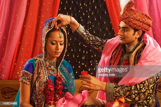 Couple performing Sindoor Daan ceremony in wedding mandap