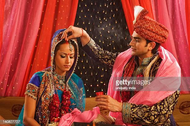 Couple performing Sindoor Daan ceremony in wedding mandap