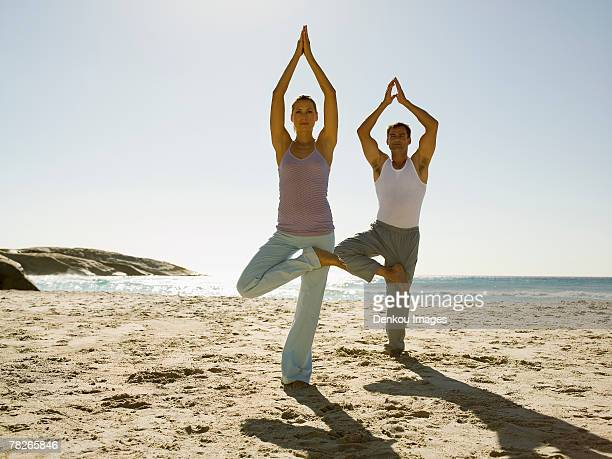 A couple performing yoga on a beach.