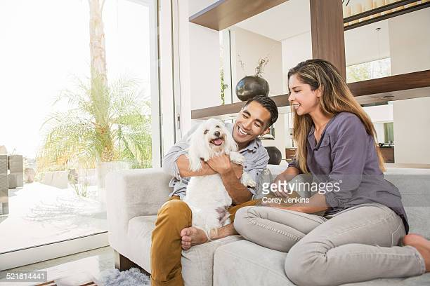 Couple petting cute dog on sitting room sofa
