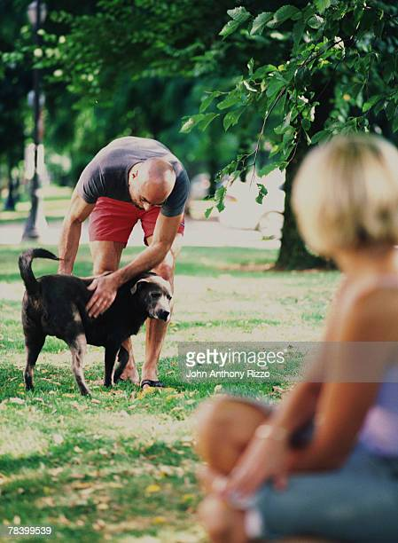 Couple petting dog in dog park