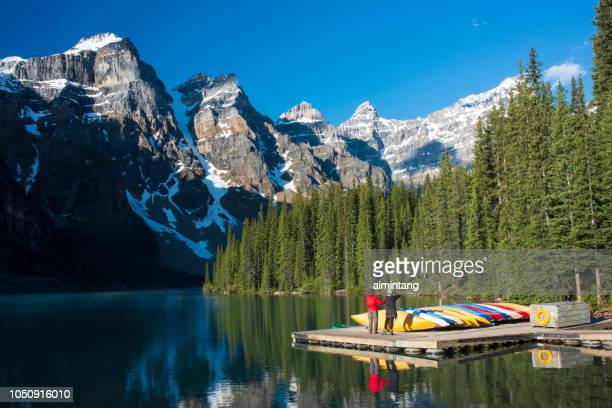 a couple photographing ten peaks in the morning at moraine lake in banff national park - valley of the ten peaks stock pictures, royalty-free photos & images