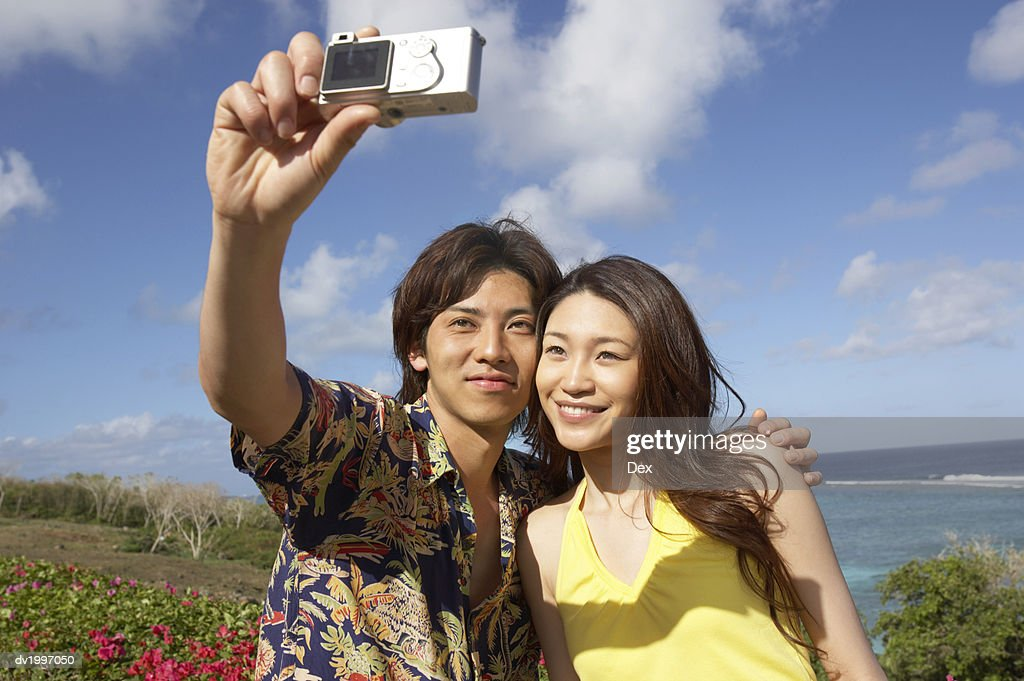 Couple Photographing Themselves on a Beach : Stock Photo