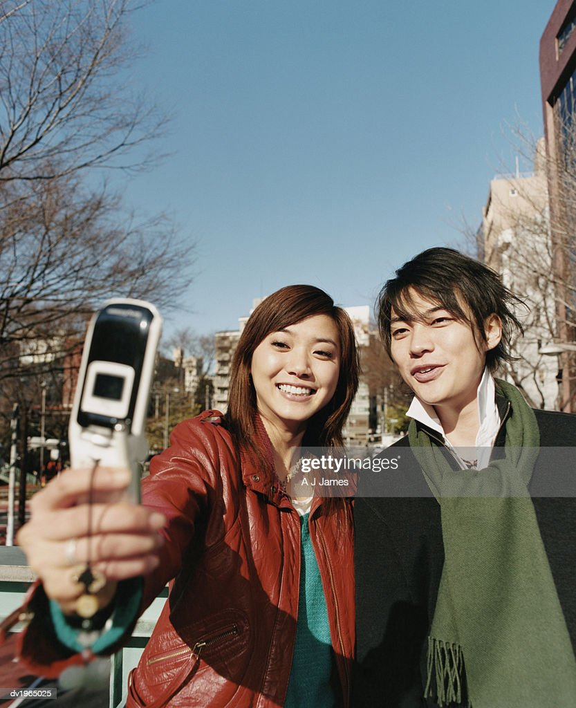 Couple Photographing Themselves with a Video Phone : Stock Photo