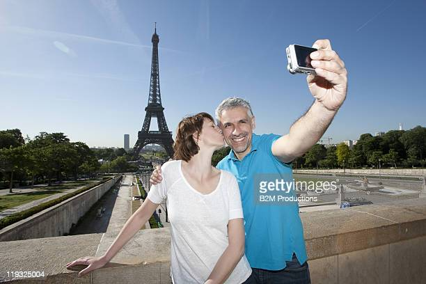Couple Photographing Themselves with Eiffel Tower