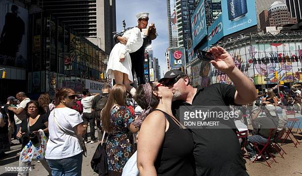 A couple photographs themselves kissing in Times Square near the a sculpture at the site of the historic LIFE Magazine cover photograph of an...