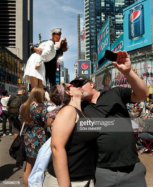 Couple photographs themselves kissing in Times Square near the a sculpture at the site of the historic LIFE Magazine cover photograph, of an...