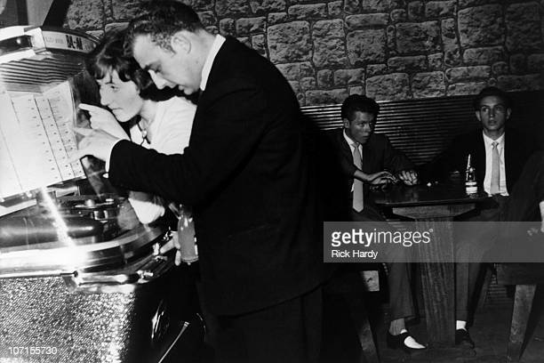 A couple pick songs on the jukebox at the 2is Coffee Bar in Soho circa 1959