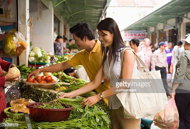 Couple picking vegetables at outdoor market, Vietnam