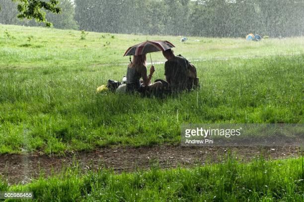 A couple picnic on Hampstead Heath London England under a Union Jack umbrella during a sudden summer rainstorm