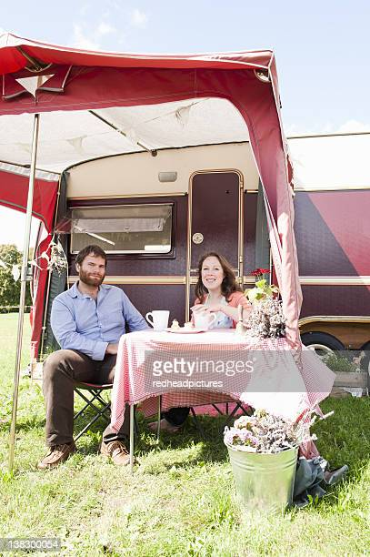 Couple picnicking outside trailer