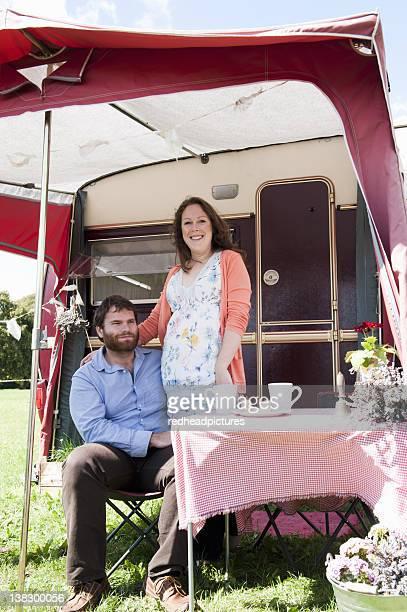 Couple picnicking outside trailer