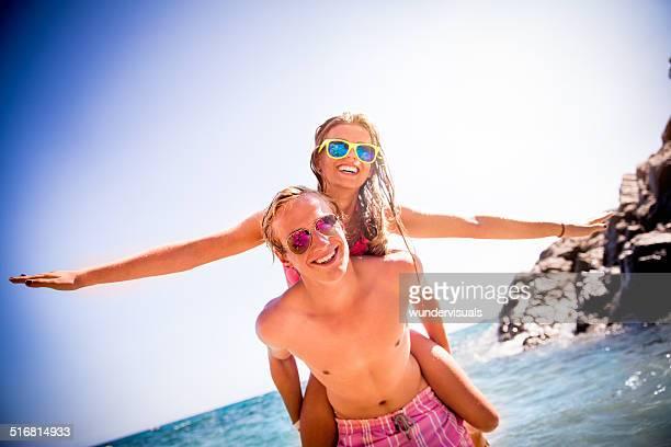 Couple Piggyback At Beach
