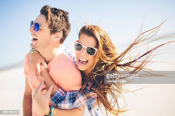 Couple piggyback on beach