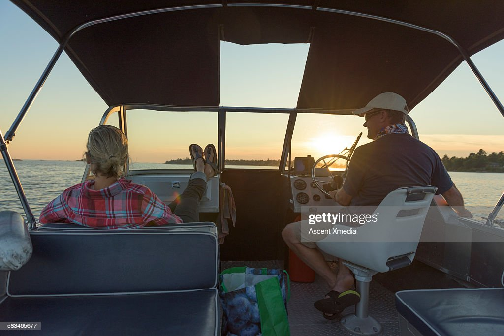 Couple pilot motorboat across tranquil lake : Stock Photo