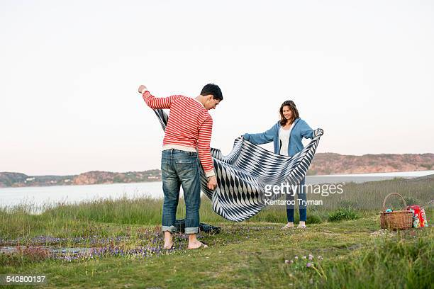 Couple placing blanket on field