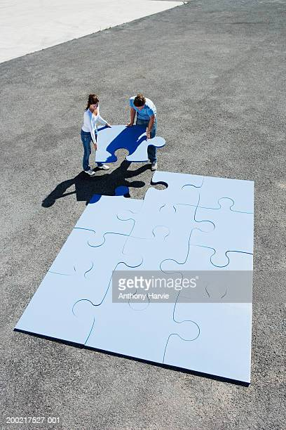 Couple placing last piece in giant jigsaw puzzle, elevated view
