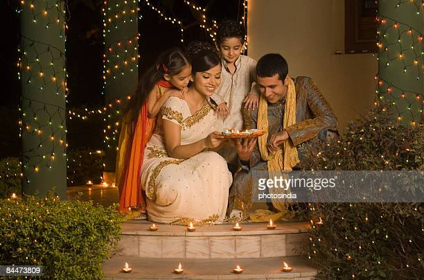 couple placing oil lamps on doorstep with their children - diwali stock photos and pictures
