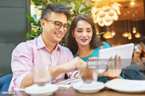 Couple planning with digital tablet computer in street cafe KL Malaysia