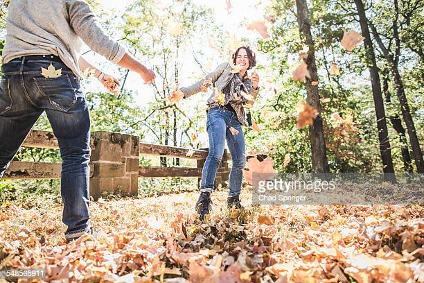Couple play fighting kicking autumn leaves in forest