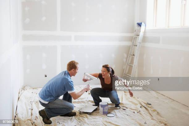 couple play fighting while painting - rough housing stock photos and pictures