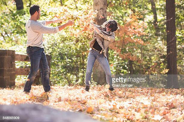 Couple play fighting with autumn leaves in forest
