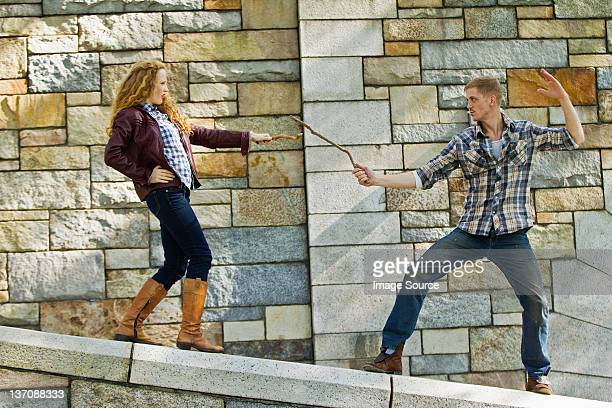Couple play fighting with sticks against stone wall