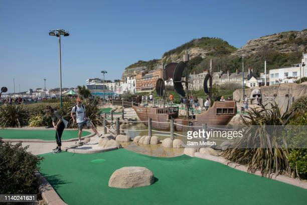 A couple play miniature golf on the 20th April 2019 in Hastings in the United Kingdom Hastings is a town on Englands southeast coast it's known for...