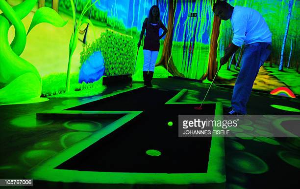 A couple play minigolf in a blacklight minigolf hall in Berlin's Kreuzberg district on September 17 2010 The minigolf hall is designed by artist...