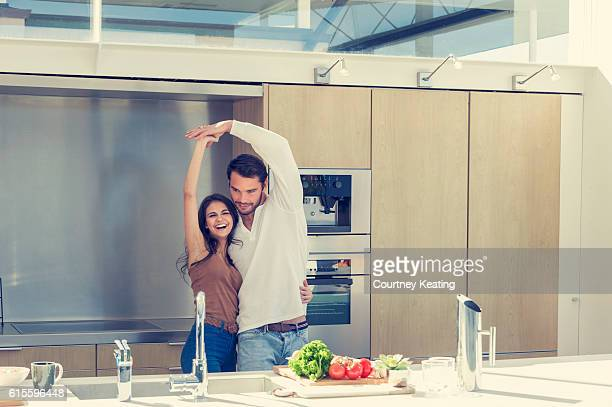 Couple playfully dancing in the kitchen.