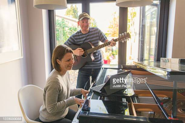 couple playing a song together whilst video conferencing friends - songwriter stock pictures, royalty-free photos & images