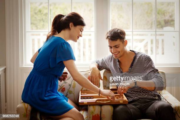 couple playing backgammon while sitting on armchair at home - バックギャモン ストックフォトと画像