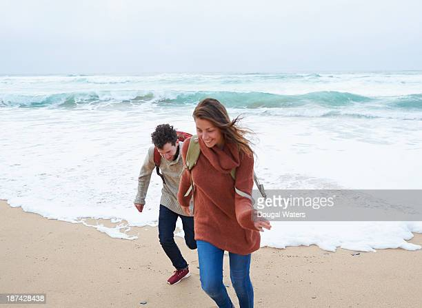 Couple playing beside beach.