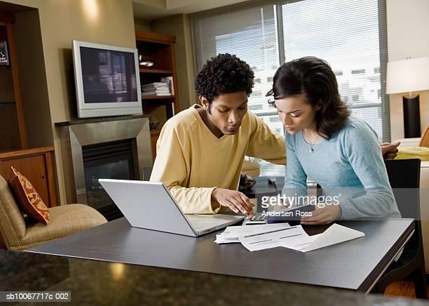Couple playing bills using laptop