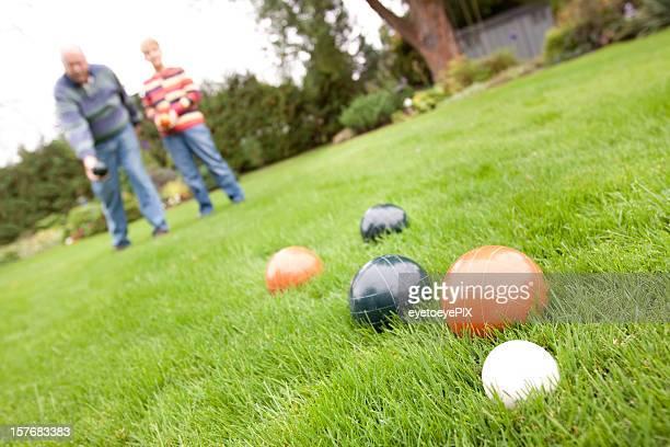 Couple playing bocce ball - horizontal