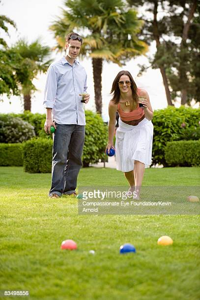 Couple playing bocce ball on lawn.