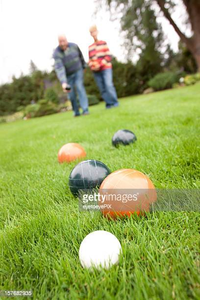 Couple playing bocce ball - vertical