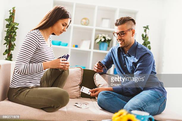 Couple playing cards in living room