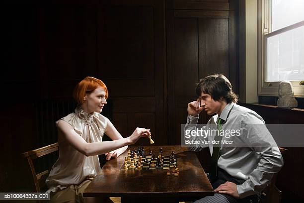 Couple playing chess at table, side view