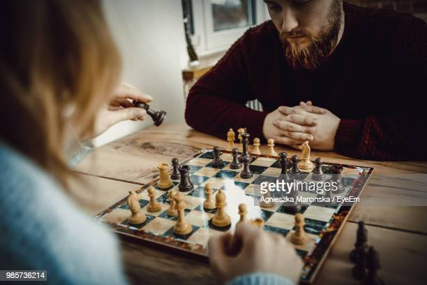couple playing chess on table at home - playing chess stock pictures, royalty-free photos & images