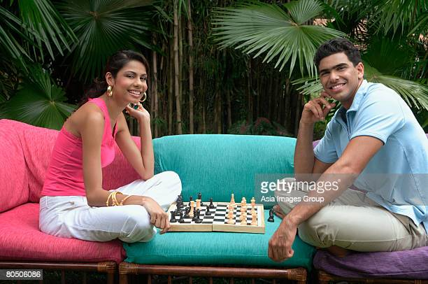 Couple playing chess outdoors, smiling at camera