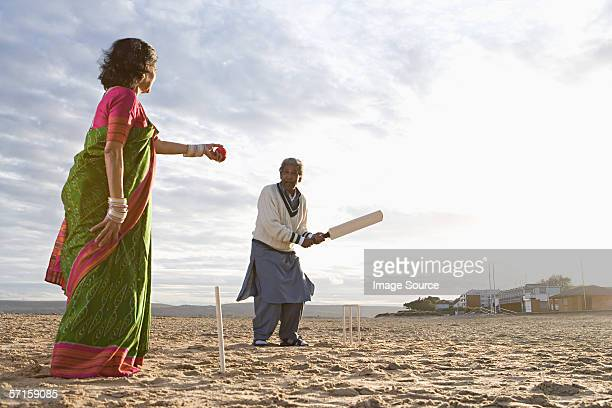 couple playing cricket on the beach - beach cricket stock pictures, royalty-free photos & images