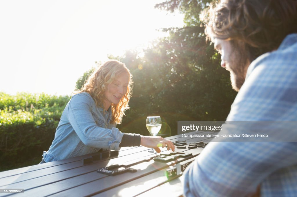 Couple playing dominoes at campsite picnic table : Stock Photo
